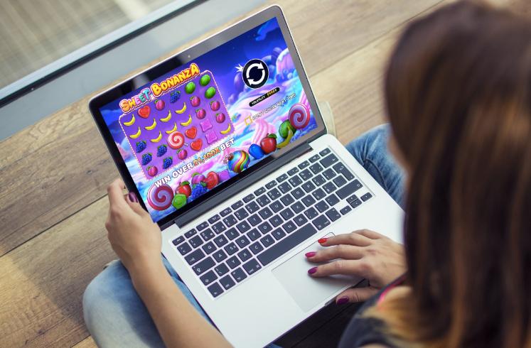 woman playing the sweet bonanza slot on a laptop
